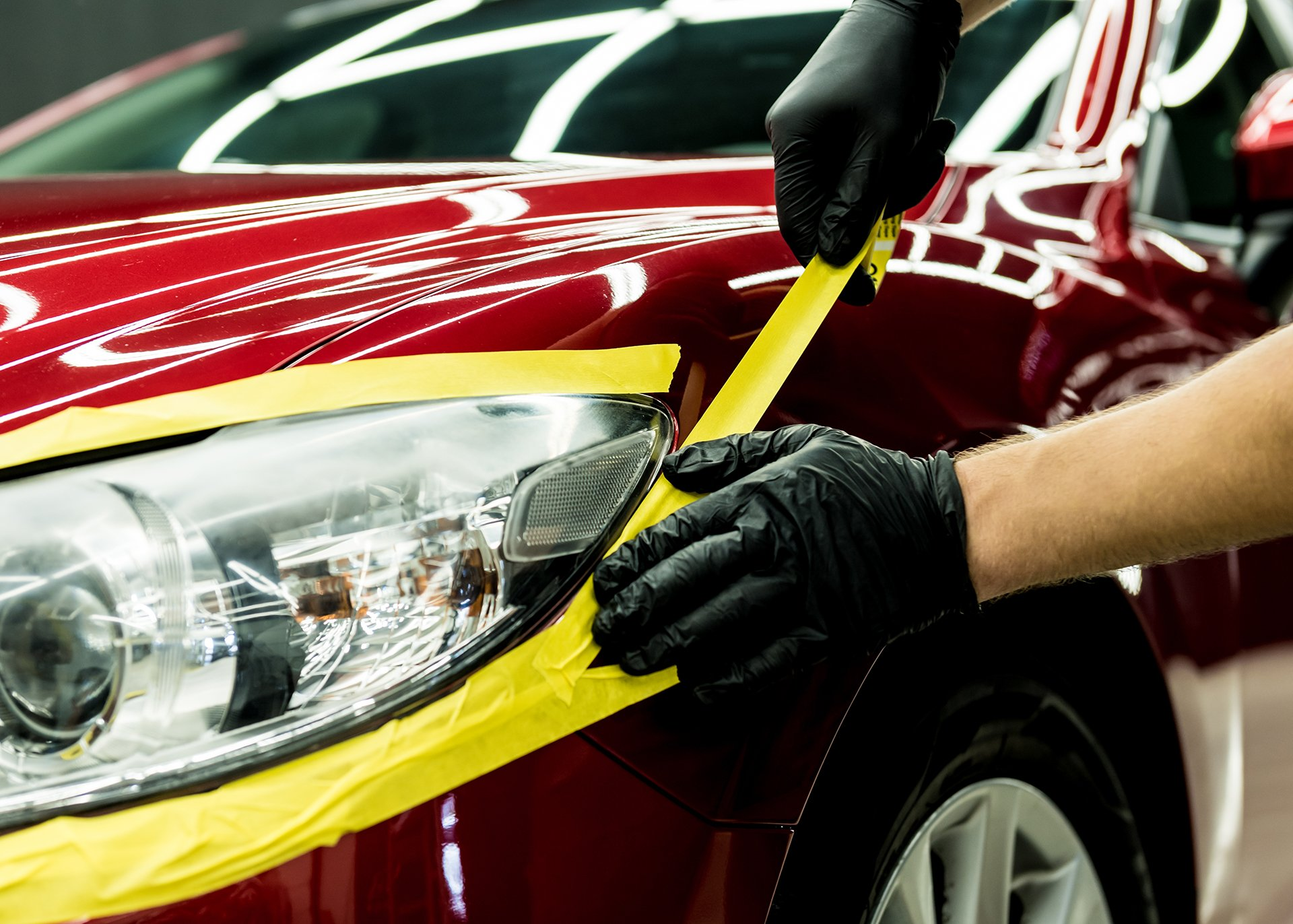 car-service-worker-applying-protective-tape-car-details-before-polishing