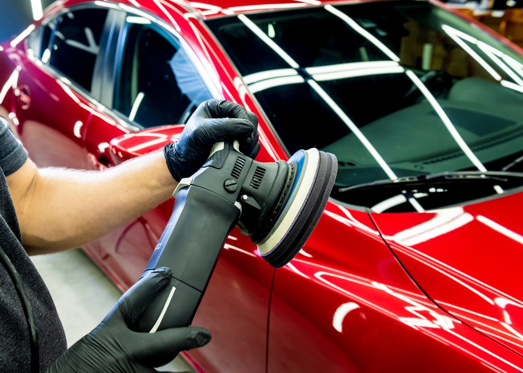 car-service-worker-polishes-car-details-with-orbital-polisher
